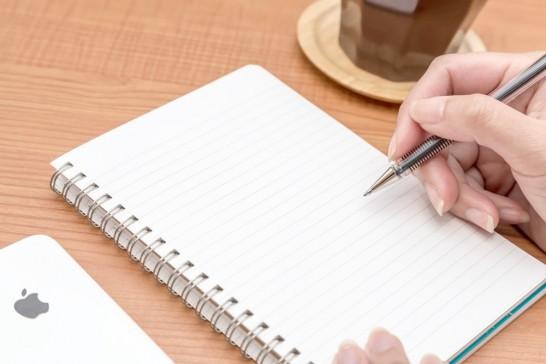 ノートにペンで文字を書こうとしている様子