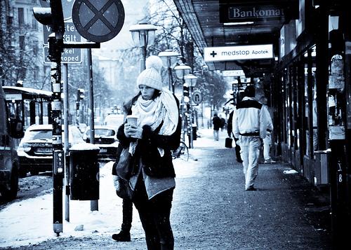 雪の降る中、コーヒー片手に寒そうな外国人女性
