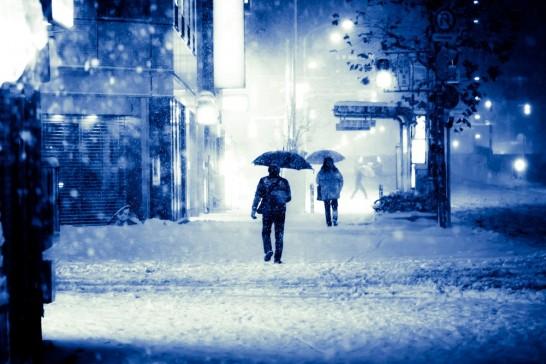 雪の中を傘をさして歩く男性